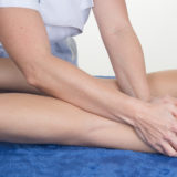 Close up of a tight of a woman massaging by therapist